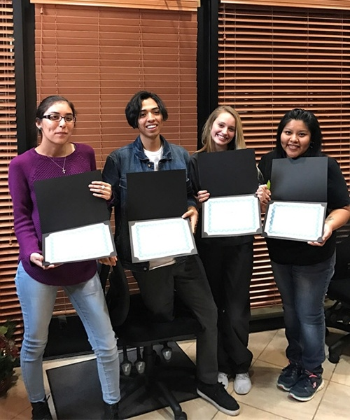 Four students with diplomas
