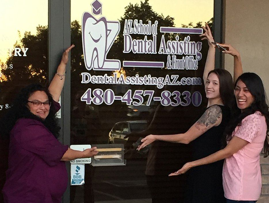 Three dental assistant trainees in front of dental school sign
