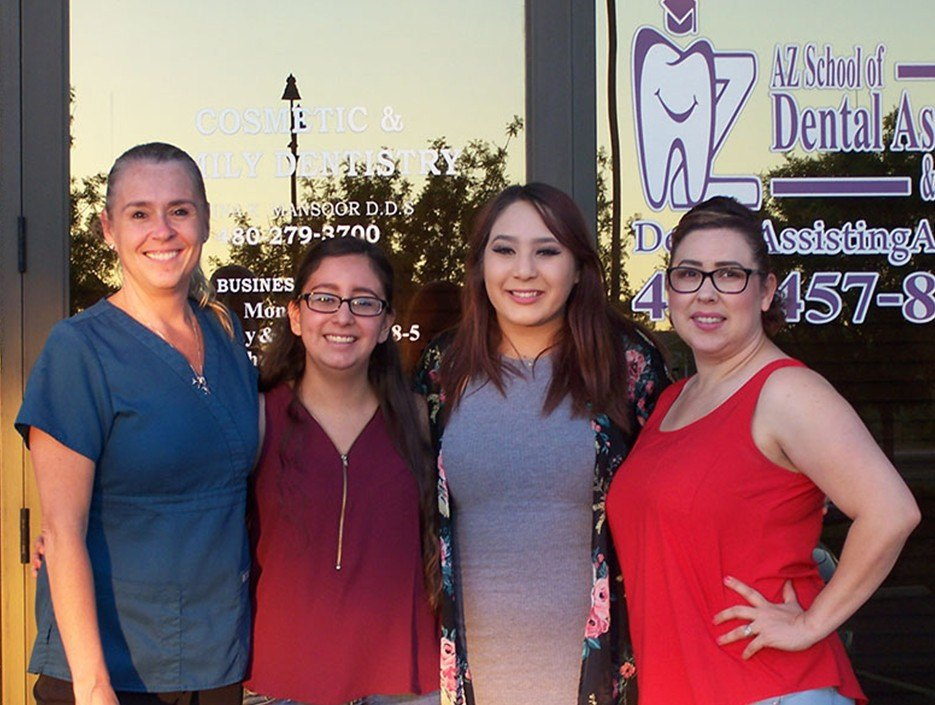 Four dental assisting school students in front of school building