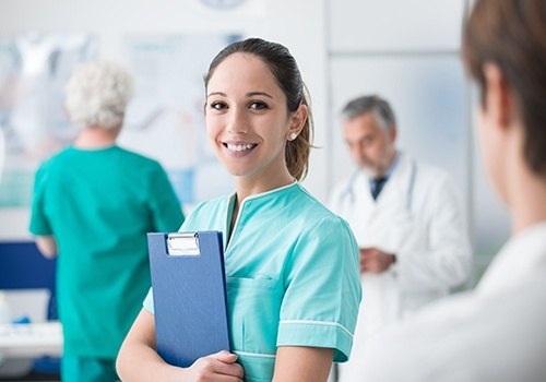 Dental assistant holding patient chart