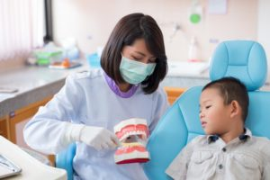 dental assistant showing a child how to brush their teeth