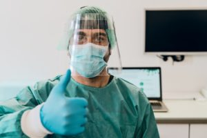 dental assistant in PPE giving a thumbs-up