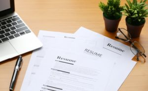 a resume on a desk next to two potted plants