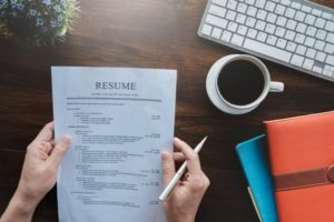 a person holding a resume in front of them with a cup of coffee next to their hand