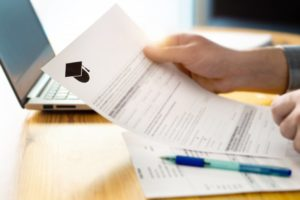 a person holding an application to dental assisting school in their hands